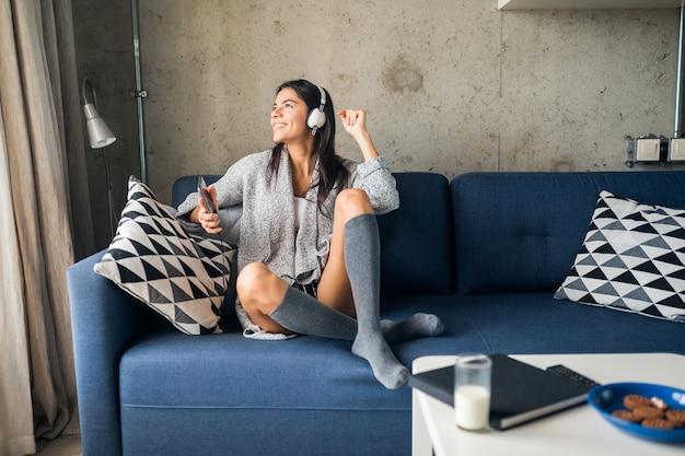 Mulher sorridente atraente e feliz sentada no sofá em casa ouvindo música nos fones de ouvido e dançando se divertindo, vestida com roupa casual