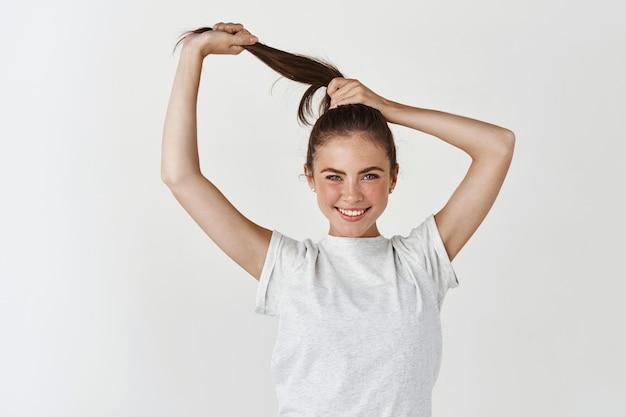 Mulher sorridente atraente mostrando cabelo longo, saudável e forte, parecendo atrevida na frente, em pé sobre uma parede branca