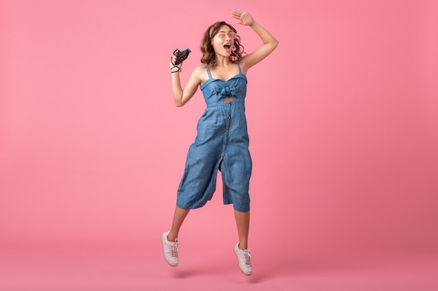 Mulher sorridente atraente pulando foto ativa na câmera vintage com vestido jeans isolado no fundo rosa