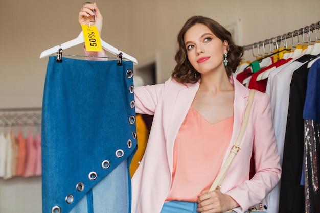 Mulher sorridente atraente segurando saia jeans no cabide em loja de roupas