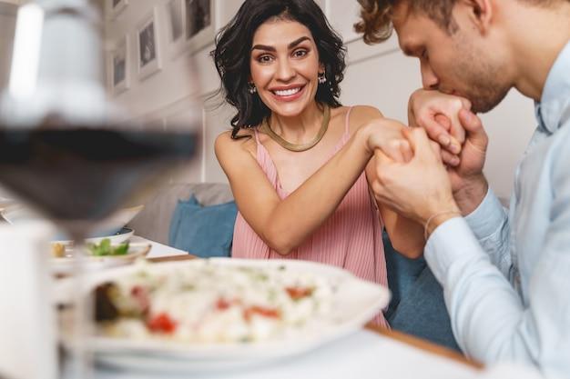 Mulher sorridente atraente tendo um encontro romântico com o namorado em restaurante