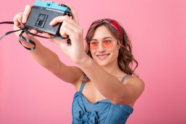 Mulher sorridente atraente tirando foto de auto-retrato na câmera vintage usando vestido jeans e óculos escuros isolados no fundo rosa