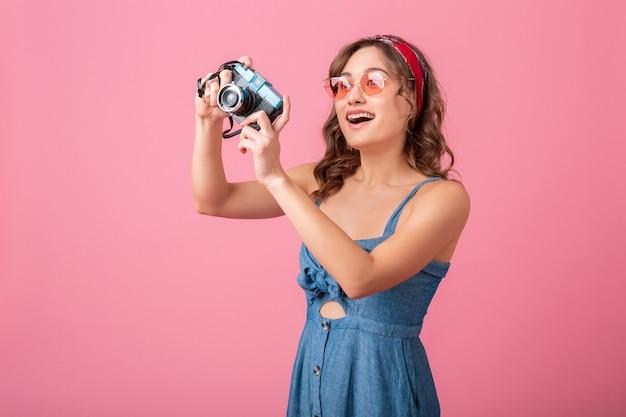 Mulher sorridente atraente tirando foto em uma câmera vintage usando vestido jeans e óculos escuros, isolado no fundo rosa