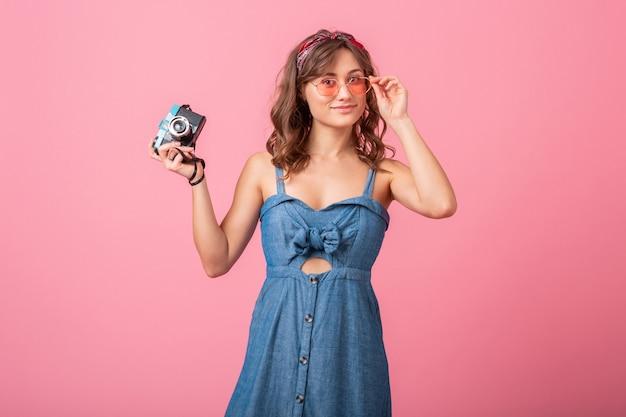 Mulher sorridente atraente tirando foto na câmera vintage, apontando o dedo para cima, usando vestido jeans e óculos escuros isolados no fundo rosa