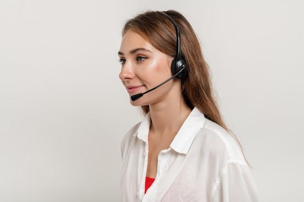 Mulher sorridente atraente trabalhando com fone de ouvido como despachante de suporte técnico isolado sobre o branco