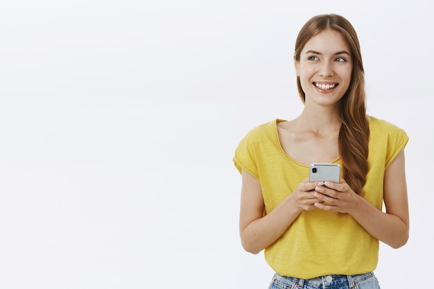 Mulher sorridente atraente usando telefone celular, mensagem de texto no aplicativo ou rede social
