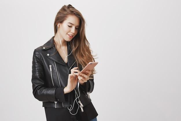 Mulher sorridente atraente usando telefone celular, ouvindo fones de ouvido música