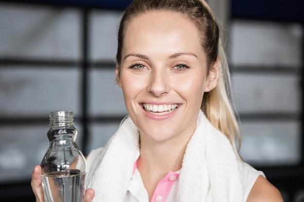 Mulher sorridente, bebendo, água, em, a, ginásio