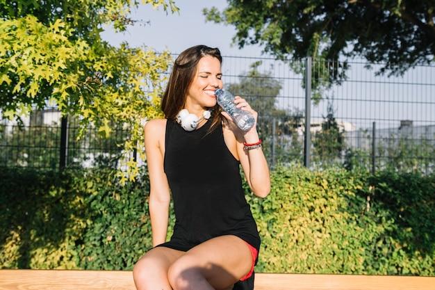 Mulher sorridente, bebendo, água, em, ao ar livre