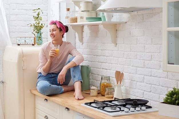 Mulher sorridente bebendo suco de laranja na cozinha