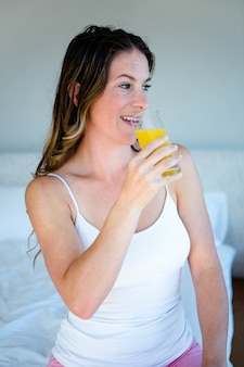 Mulher sorridente, bebendo um copo de suco de laranja, sentada na cama dela