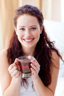 Mulher sorridente, bebendo, um, xícara chá, em, quarto