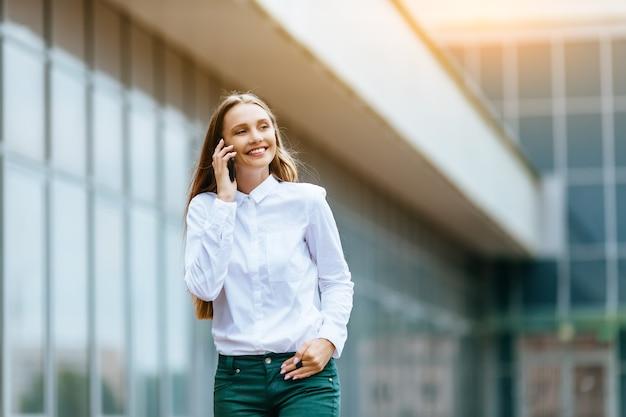 Mulher sorridente bem-sucedida falando ao telefone ao ar livre de um prédio de escritórios