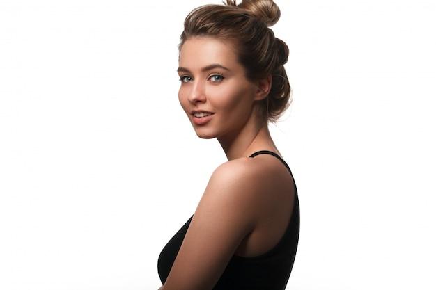Mulher sorridente bonita com pele limpa, maquiagem natural e dentes brancos em branco.