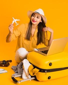 Mulher sorridente, brincando com estatueta de avião