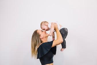 Mulher sorridente brincando com o bebê