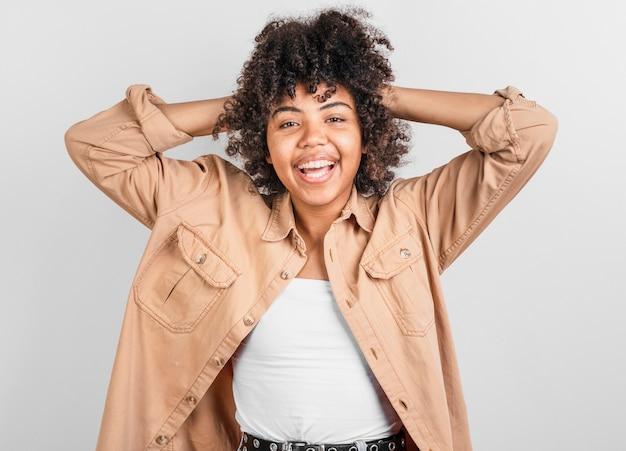 Mulher sorridente, brincando com o cabelo dela