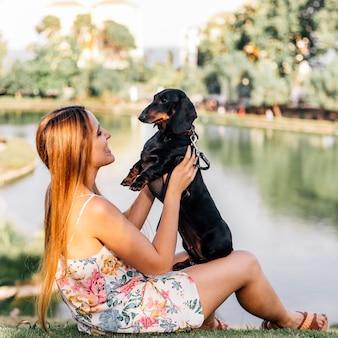 Mulher sorridente brincando com seu cachorro perto do lago