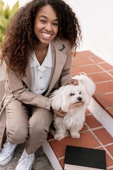 Mulher sorridente, brincando com um cachorro ao lado de seu livro