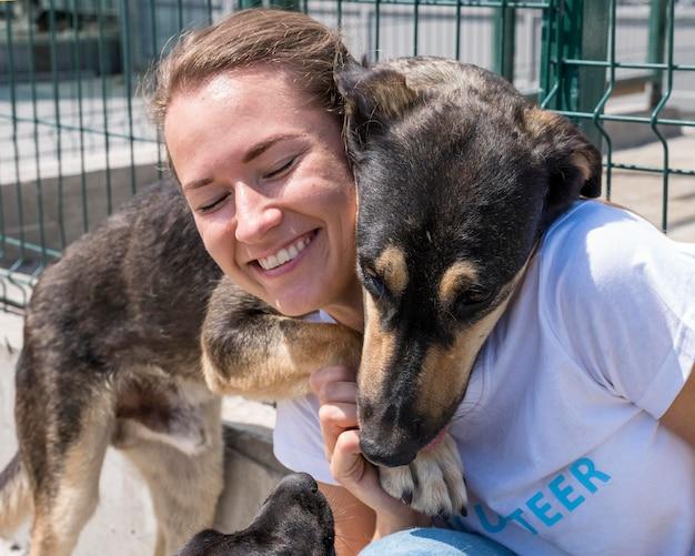 Mulher sorridente brincando com um cachorro fofo para adoção