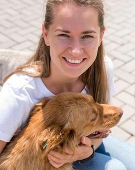 Mulher sorridente brincando com um cachorro no abrigo