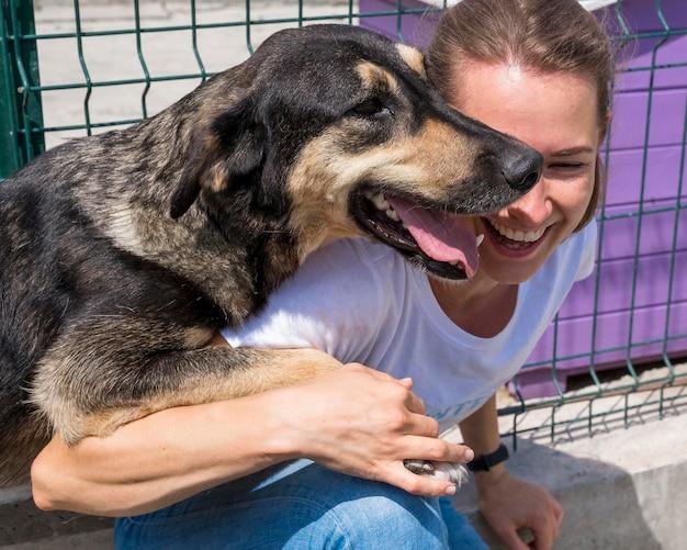 Mulher sorridente brincando com um cachorro para adoção