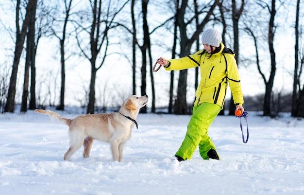 Mulher sorridente brincando com um lindo cachorro retriever jovem na natureza de inverno
