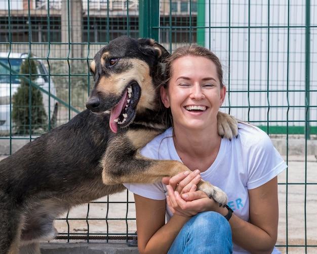 Mulher sorridente brincando no abrigo com um cachorro esperando para ser adotado