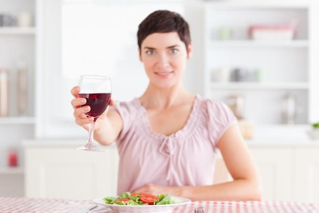 Mulher sorridente brindando com vinho