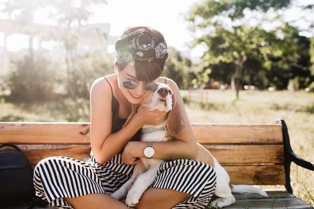 Mulher sorridente bronzeada em um elegante relógio de pulso abraçando um cachorro beagle durante o descanso no parque pela manhã