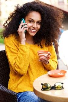 Mulher sorridente, café bebendo, e, usando, telefone móvel