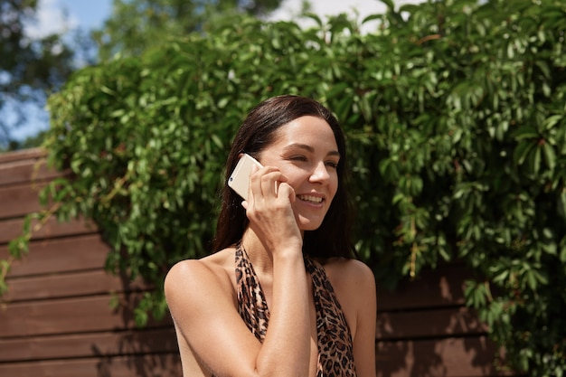 Mulher sorridente calma em traje de banho com estampa de leopardo em pé perto de árvores verdes e falando no smartphone durante um dia de sol, descansando no resort