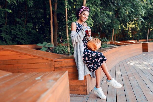 Mulher sorridente caminhando em um parque ensolarado e bebendo limonada
