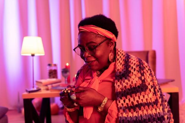 Mulher sorridente. cartomante rechonchudo afro-americano usando grandes anéis e sentindo-se satisfeito enquanto está sentado em um salão de adivinhação
