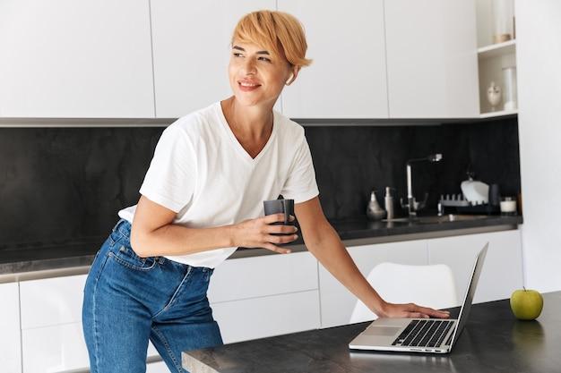 Mulher sorridente, casual vestida usando um laptop, em pé na cozinha, usando fones de ouvido