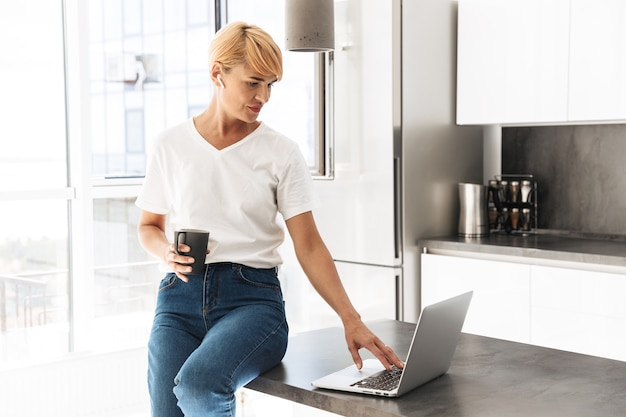 Mulher sorridente casual vestida usando um laptop enquanto está sentada na cozinha, usando fones de ouvido