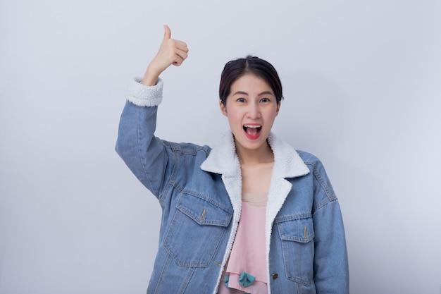 Mulher sorridente caucasiana, mostrando a mão polegares para cima em bom trabalho conceito, menina asiática positiva vestindo roupas casuais azuis