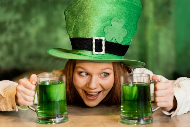 Mulher sorridente celebrando st. dia de patrick com bebidas
