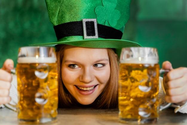 Mulher sorridente celebrando st. dia de patrick no bar com bebidas