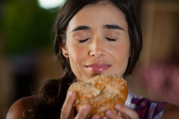 Mulher sorridente cheirando um pão no balcão
