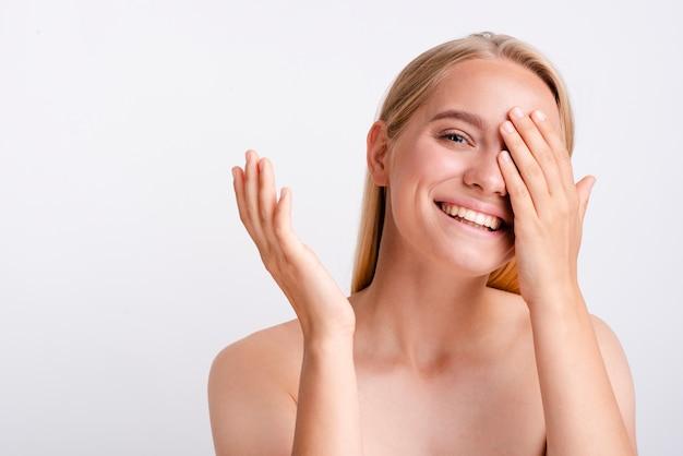 Mulher sorridente close-up, cobrindo o olho com uma mão