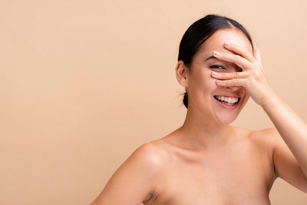 Mulher sorridente close-up, cobrindo os olhos com cópia-espaço