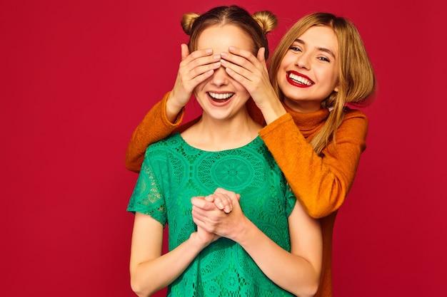 Mulher sorridente, cobrindo os olhos com as mãos para a amiga