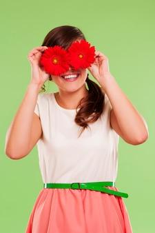 Mulher sorridente cobrindo os olhos com duas flores