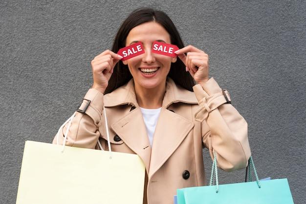 Mulher sorridente cobrindo os olhos com etiquetas de liquidação enquanto segura sacolas de compras