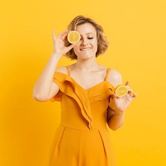 Mulher sorridente, cobrindo os olhos com uma fatia de limão