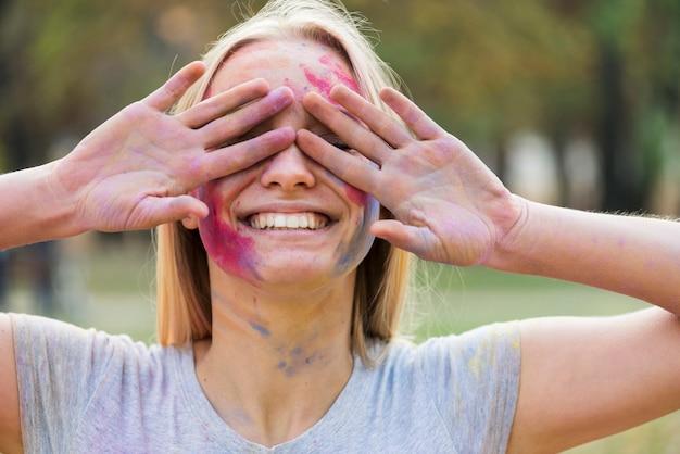 Mulher sorridente, cobrindo os olhos no festival