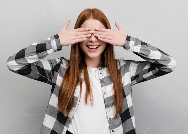 Mulher sorridente, cobrindo os olhos plano médio