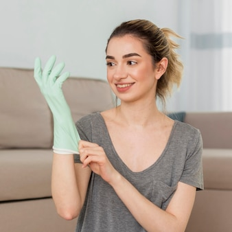 Mulher sorridente, colocando a luva de limpeza