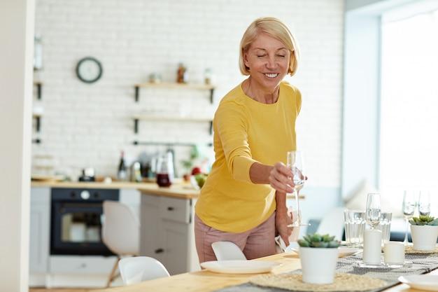 Mulher sorridente, colocando flauta na mesa